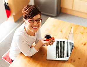 Woman drinking coffee in front of laptop